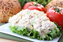 picture of chicken salad on a piece of lettuce, sitting on a plate