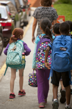 Young kids with backpacks headed to school.