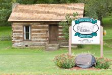 Pioneer Village welcome sign in front of a log cabin.