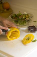 Cutting a yellow pepper.