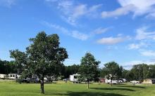 View of Woodside campground with blue sky and trees.