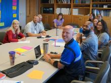 Group of people sitting around a conference table turning and smiling at the camera.