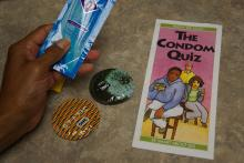 a hand holding a Condom Quiz brochure next to two condom wrappers