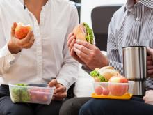 Group of people eating fruit and sandwiches.