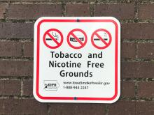 "Sign on a wall that reads ""Tobacco and Nicotine Free Grounds""."