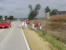 Volunteers cleaning up along roadside.