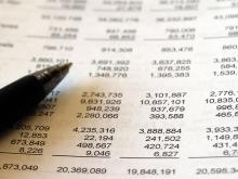 Closeup of a pen over non descript table of numbers.