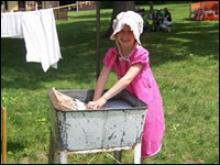 Girl washing cloths in a tub of water.