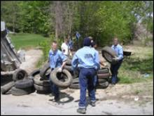Inmates cleaning up tires.