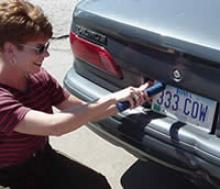 Seller is removing a license plate.