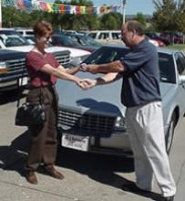 Seller and car dealer shaking hands and handing over keys.