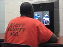 An inmate watching at a monitor for video court.