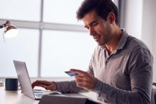 This is a man holding a credit card while sitting at a laptop computer.
