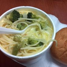 Soup in a bowl with a roll.