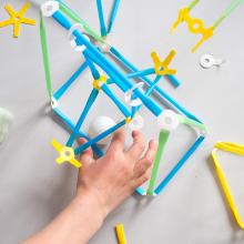 A child's hand building with a Strawbees inventor kit.