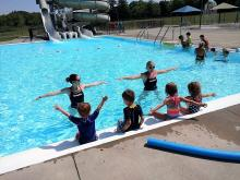Two instructors in the pool demonstrating a skill to a group of children sitting along the edge of the pool.