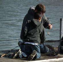 Picture of a grown man and child on a boat dock with trout in a fishing net.