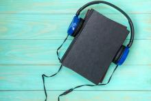 Headphones put over hardback book with empty cover on blue wooden background