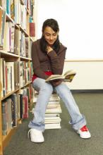 Girl reading while sitting atop stack of books in library