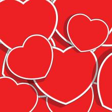 Red hearts of various sizes in a pile.