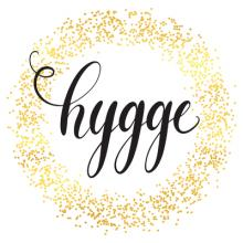 "The word ""hygge"" surrounded by a gold, glittery circle."