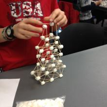 A child building with marshmallows and toothpicks.