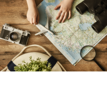 Map, magnifying glass, binoculars, and camera on a table