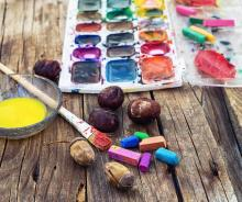 set of different paint colors and brush for painting on wooden background