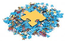 one big yellow piece on pile of disassembled little blue jigsaw puzzles isolated on white background