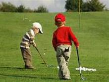 photo of 2 young boys on on golf green