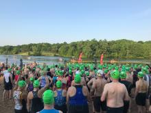 Large group of race participants waiting to enter the lake for the swim portion or the event.