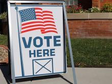 "Sidewalk sign that reads ""Vote Here"""