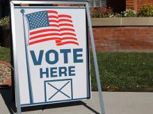 """Sign that reads """"Vote Here""""."""