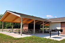 Side view of picnic shelter with two charcoal grills.