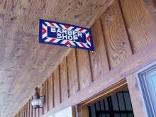 Barber shop sign hangs outside the door.