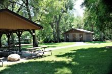 Side view of picnic shelter with sand volleyball and modern restroom in background.