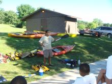 Instrutor demonstrating how to use a kayak paddle.