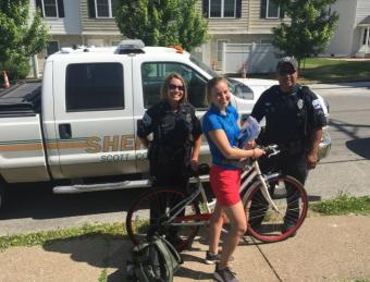 Police officers with a girl on a bike.