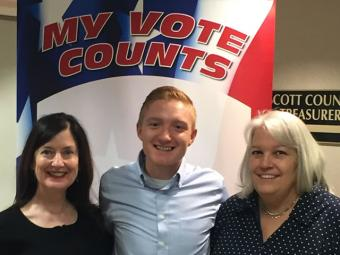 Three voters posing for a selfie in front of the my vote counts poster.