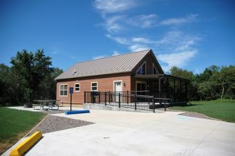 Full view of cabin with parking spaces and patio with picnic tables and fire ring.