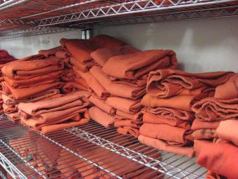 Shelf of folded standard issue jail clothing.