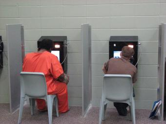 Inmates on the video conference with counterparts in the visitation room.