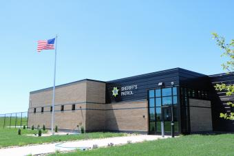 Sheriff Patrol Headquarters building with flag flying in foreground.