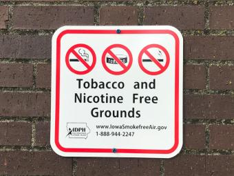 """Sign on a wall that reads """"Tobacco and Nicotine Free Grounds""""."""