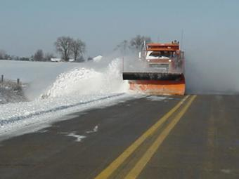 County truck plowing snow off the road into the ditch.