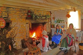 photo of people dress in old time attire sitting by a fire