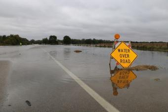 """""""Water Over Road"""" sign on roadway submerged in water."""