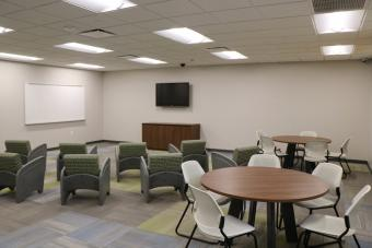 Chairs and tables facing a white board and TV in the new program area.