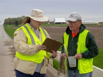 Volunteers reviewing water data on clipboard.