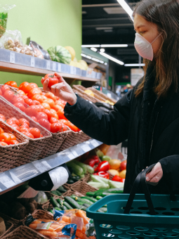 This is an image of a woman shopping for vegetables wearing a medical face mask.